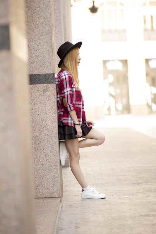 Camisa con estampado tartán de H&M y falda de cuero de Bershka